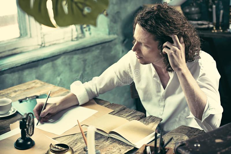 Writer at work. Handsome young writer sitting at the table and writing something in his sketchpad stock photos