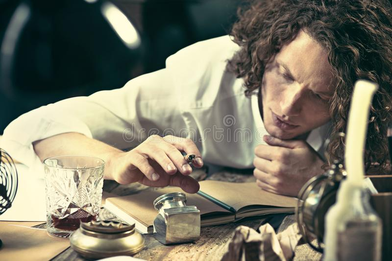 Writer at work. Handsome young writer sitting at the table and writing something in his sketchpad royalty free stock images