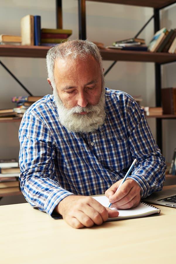 Writer working at his working place. Senior writer working at his working place stock photos
