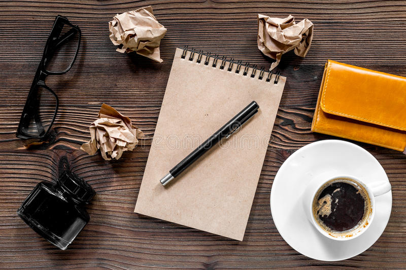 Writer workplace with vintage notebook, pen, glasses and coffee on wooden table background top view stock photos