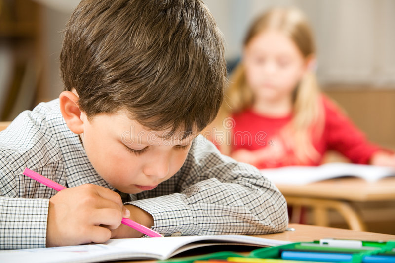 Writing. Photo of clever schoolkid writing something in his copybook at lesson on background of classmate stock image