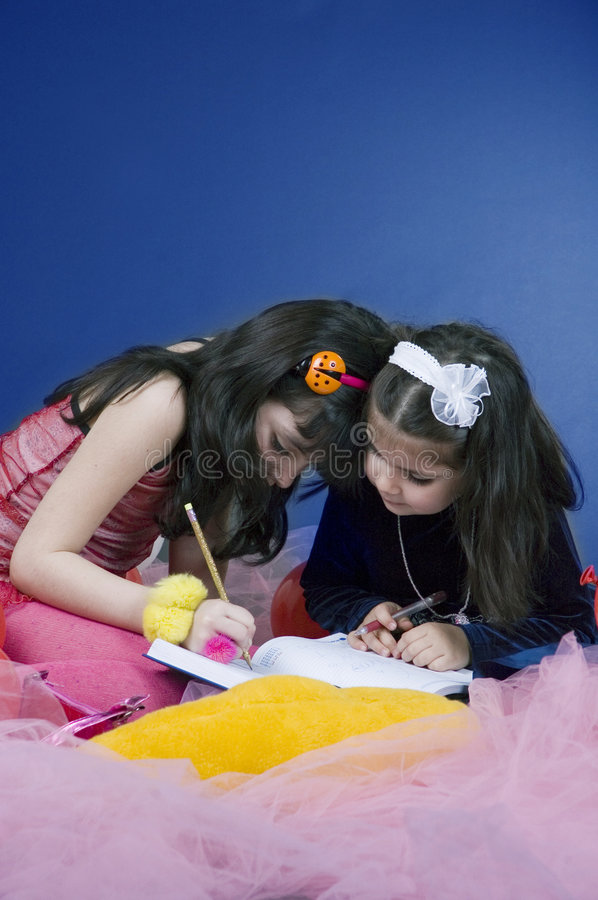 Writing in an agenda. Two little girls writing something in an agenda looking focused stock photos