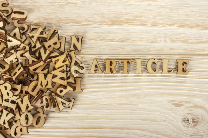 Writing articles. From the pile of letters to create the text for the press. Wooden letters on a wooden background. The view from royalty free stock photos