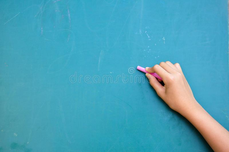 Writing on blackboard. Kid writing on blackboard with chalk stock photo