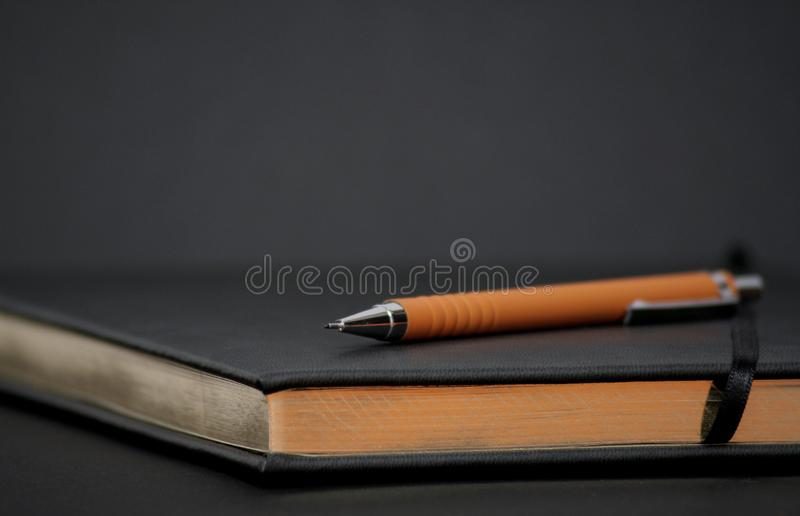 Writing book with orange pencil royalty free stock images