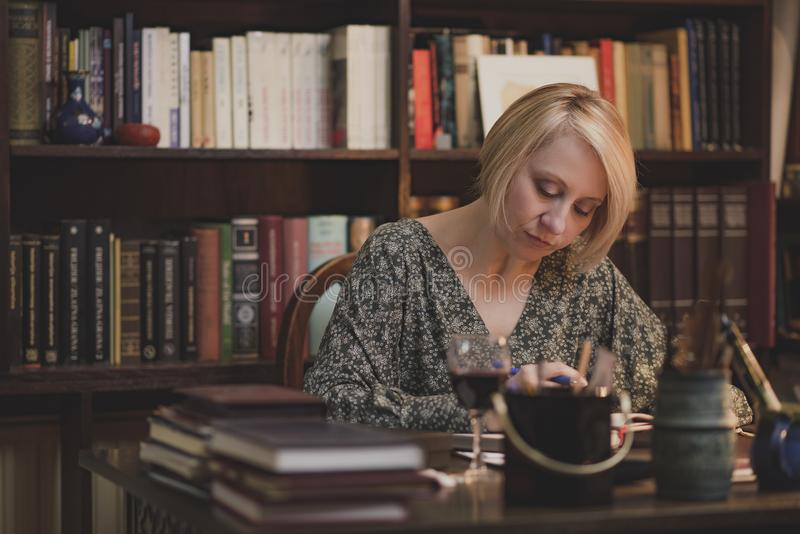 Writing a book in a personal library. Mature blonde lady writing down notes, studying or writing a book and holding a glass of wine in an intimate private royalty free stock photo