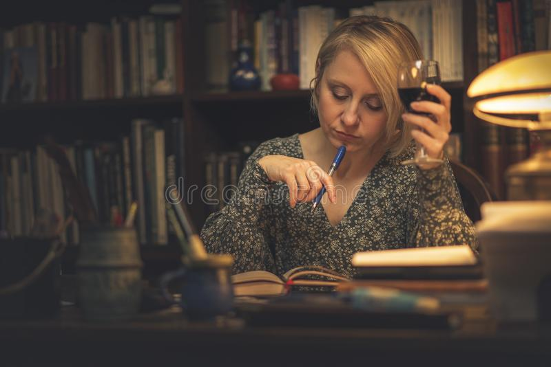 Writing a book in a personal library. Mature blonde lady writing down notes, studying or writing a book and holding a glass of wine in an intimate private royalty free stock photography
