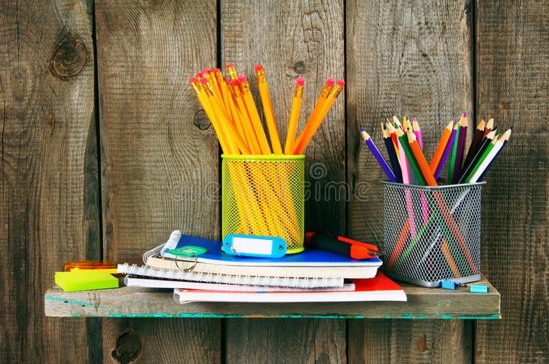 Writing-books and school tools on a wooden shelf. royalty free stock photos