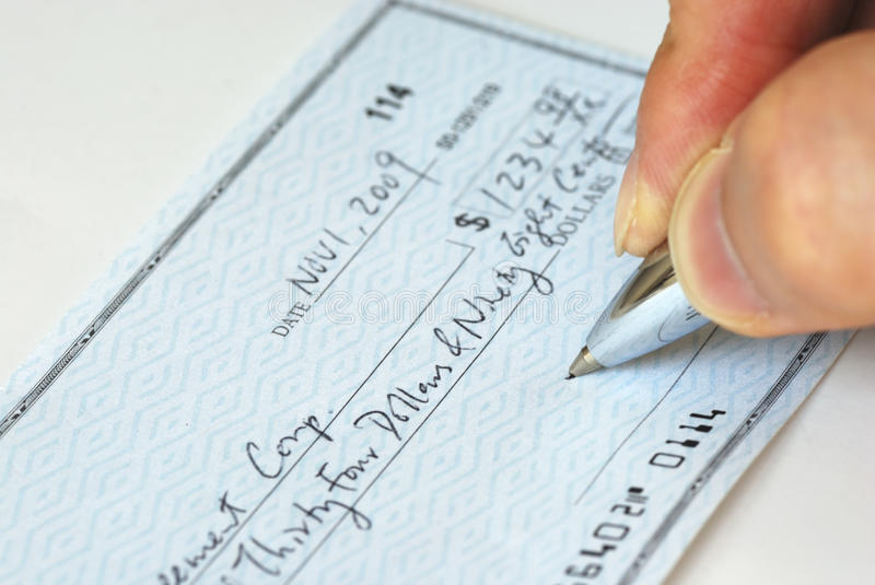 Writing a check to pay bill stock photos
