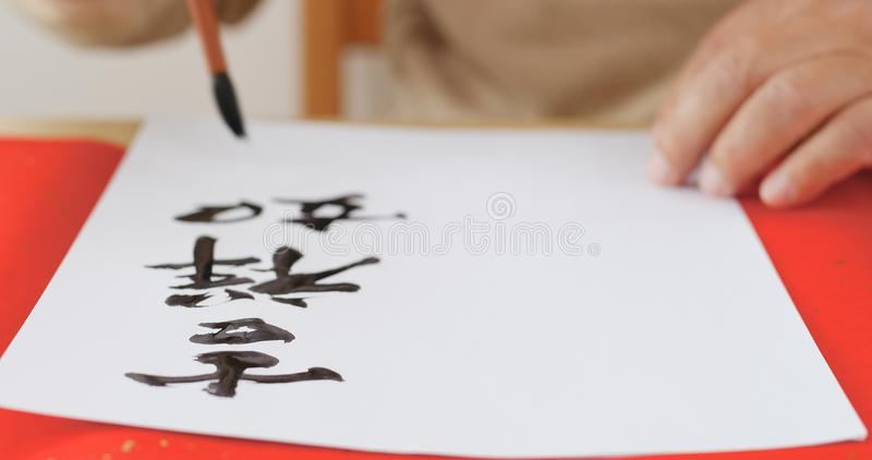Writing Chinese calligraphy with phrase meaning wish you good fortune and may all your wishes come true stock images