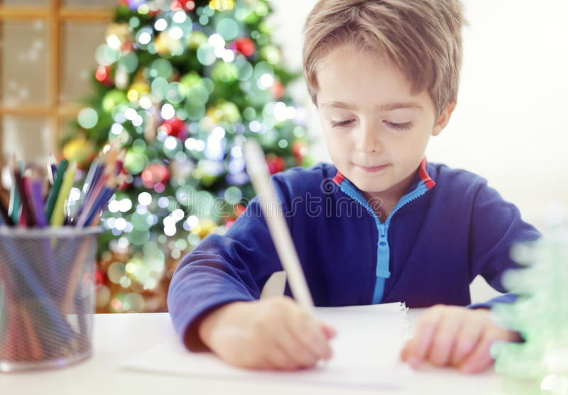 Writing a Christmas list letter to Santa Claus. Child writing a Christmas list letter to Santa Claus stock photography