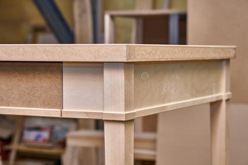 Writing desk building process. Production of wood furniture. Furniture manufacture. Close-up. Beautiful professionally made wood writing desk in process of stock image