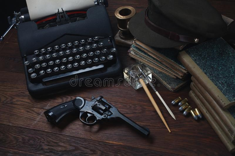 Writing a detective story - old retro vintage typewriter and revolver gun with ammunitions, books, papers, old ink pen stock images