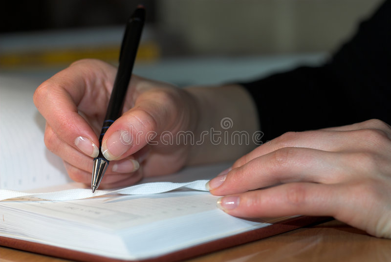 Writing in diary. Young woman is writing notes in diary stock images