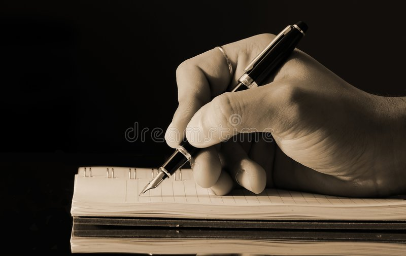 Writing in a diary. Vintage horizontal photo of a man's hand writing into a notebook using a fountain pen
