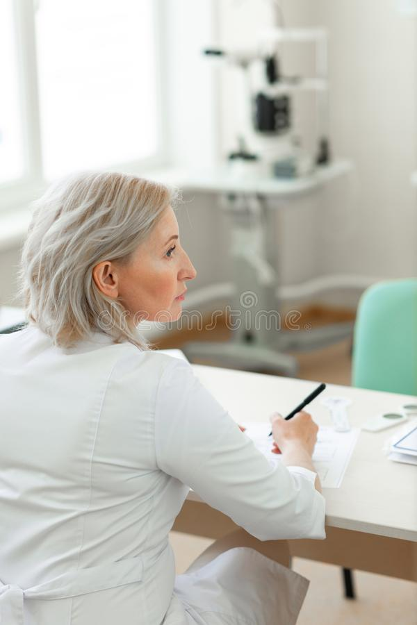 Attentive good-looking doctor in white uniform holding pan and listing. Writing down recommendations . Attentive good-looking doctor in white uniform holding pan royalty free stock images