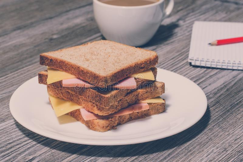 Writing essay business education food snack eating concept. Business breakfast. Tasty ham and cheese sandwich with cup of coffee, royalty free stock images