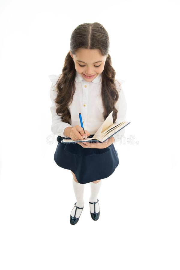 Writing essay. School girl excellent pupil prepared essay or school project. Schoolgirl wear school uniform. Knowledge. Day. Girl with copy book or workbook royalty free stock image