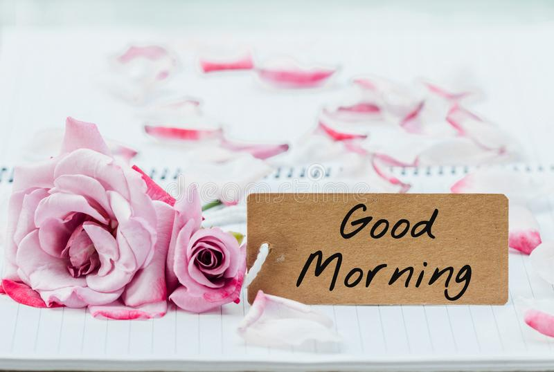 Writing good morning on card. With rose on notebook stock image