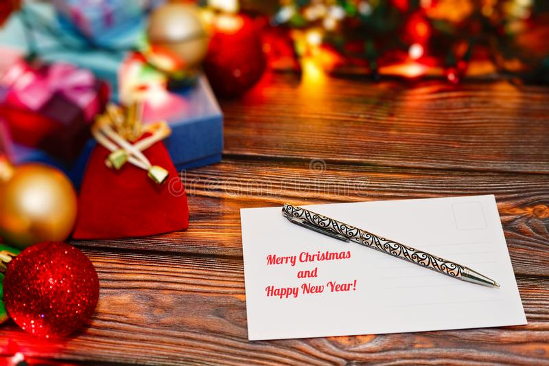 Writing holiday congratulations post cards. Preparing Christmas and New Year cards for friends and relatives with congratulations. Signed postcard and royalty free stock photos