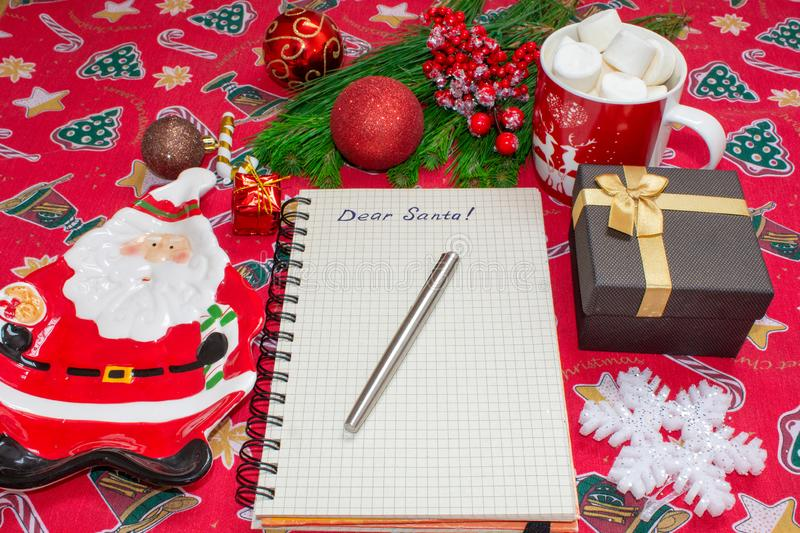 Writing a letter to Santa Claus on a festive red background with Christmas gifts, a plate in the shape of Santa Claus. A marshmallow mug and decorated top view royalty free stock photo
