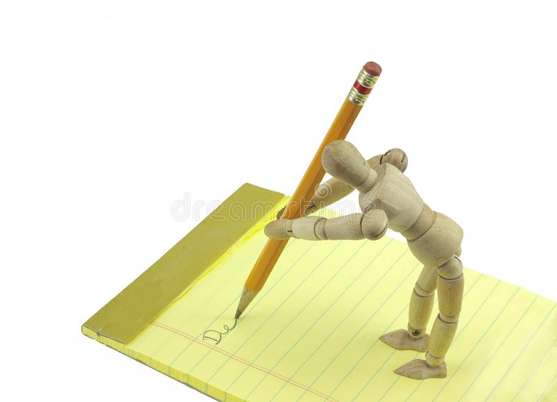 Writing mannequin. Wooden mannequin writing note to friend or loved one royalty free stock photo