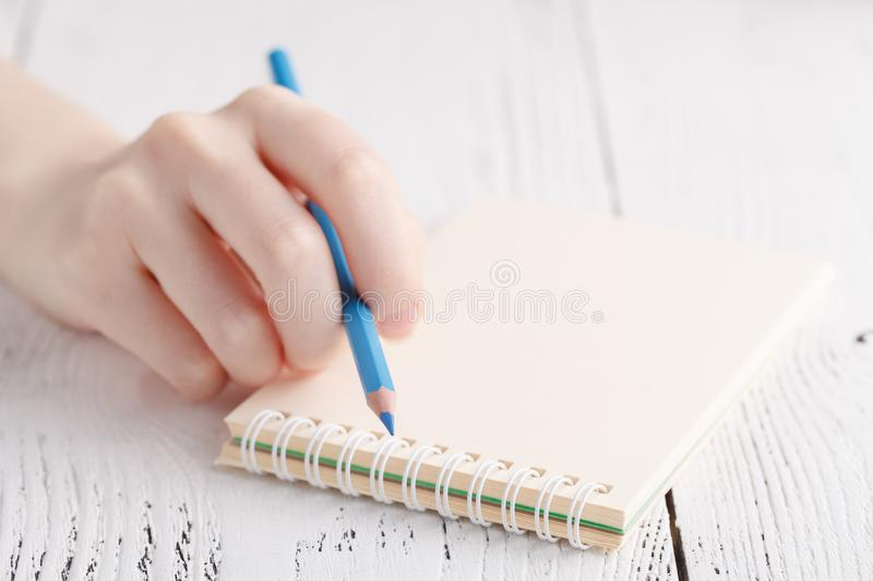 Writing memories note, close up female hand with pen royalty free stock photography