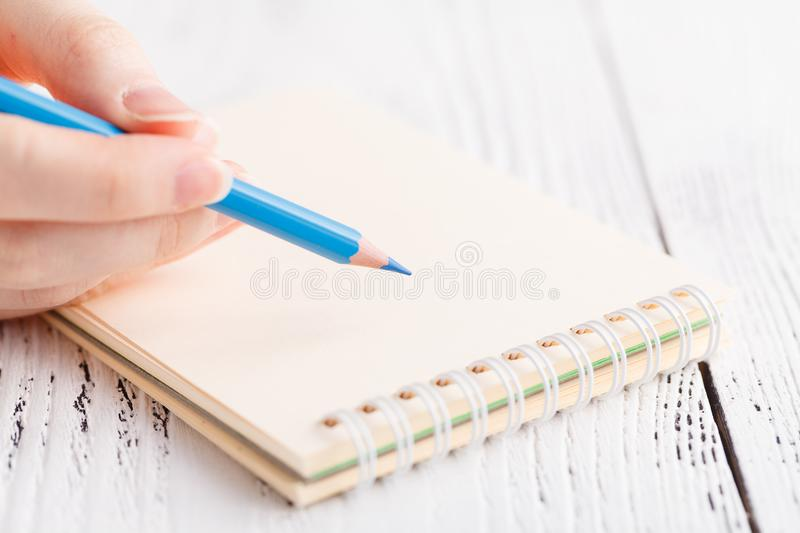 Writing memories note, close up female hand with pen royalty free stock images