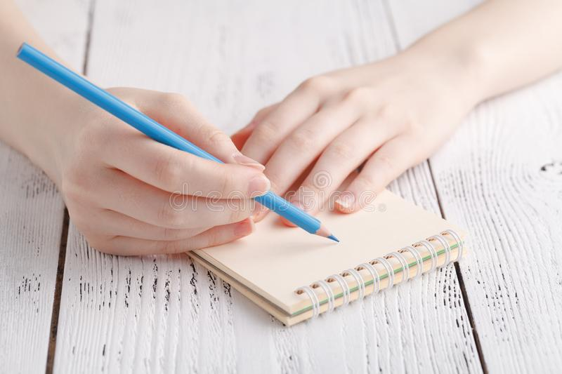 Writing memories note, close up female hand with pen stock photo