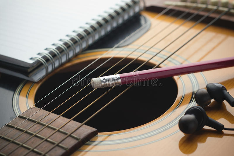 Writing music. Notebook and pencil on guitar, Writing music stock photos