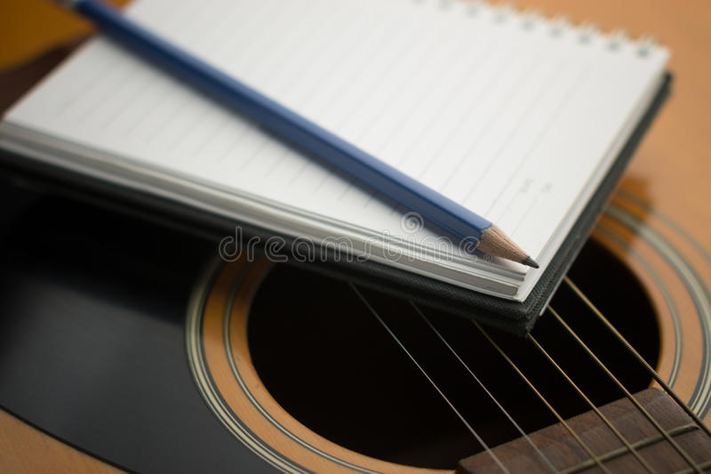 Writing music. Notebook and pencil on guitar,Writing music stock photo