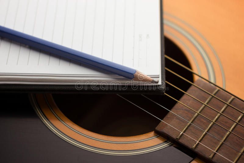 Writing music. Notebook and pencil on guitar,Writing music stock photos