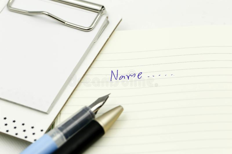 Writing the name on a paper with a pen using for concept of Namesake day.  stock photography