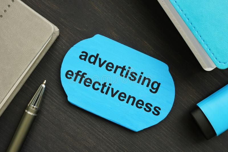 Writing note showing advertising effectiveness. The text is written on a small wooden blackboard. Markers, pen, wooden background. Are on the photo stock photo