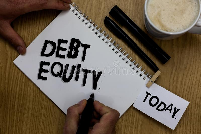 Writing note showing Debt Equity. Business photo showcasing dividing companys total liabilities by its stockholders Man holding ma. Rker notebook clothepin stock photos