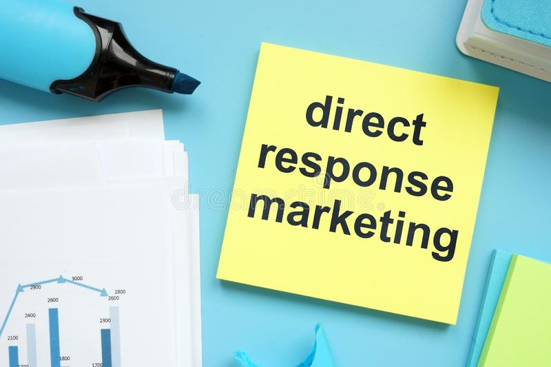 Writing note showing direct response marketing. The text is written on a small colored paper. Graphs on the paper sheet, markers, royalty free stock image