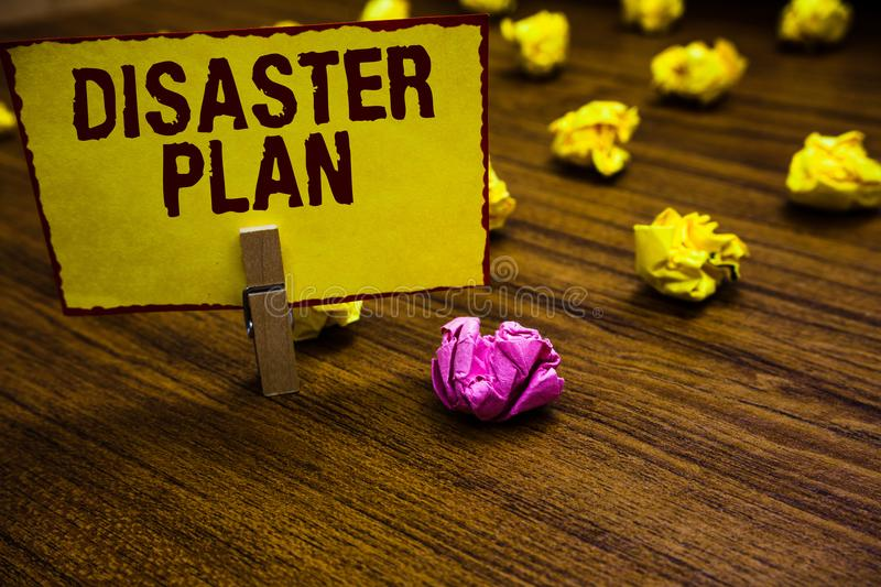 Writing note showing Disaster Plan. Business photo showcasing Respond to Emergency Preparedness Survival and First Aid Kit Clothes. Pin holding yellow paper note royalty free stock photo