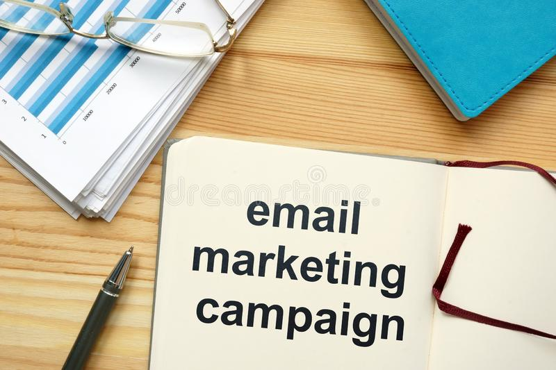 Writing note showing email marketing campaign. The text is written in the notebook. Graphs on the paper sheet, pen, wooden stock photography