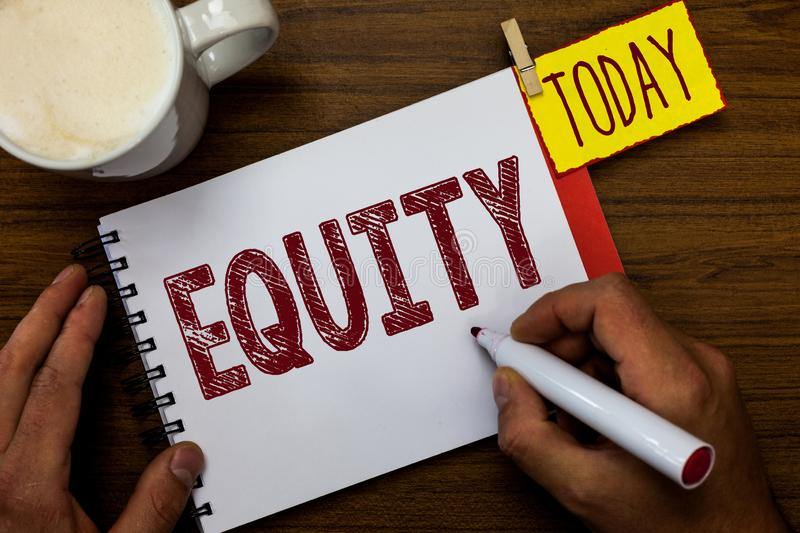 Writing note showing Equity. Business photo showcasing quality of being fair and impartial race free One hand Unity Man. Holding marker notebook pin reminder royalty free stock photo