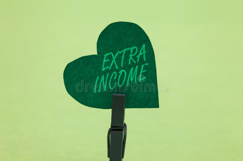 Writing note showing Extra Income. Business photo showcasing Additional fund received or earned from a non regular basis Clothespi. N holding green paper heart royalty free stock photos