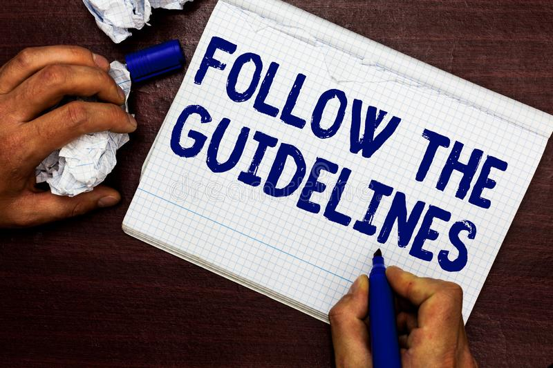 Writing note showing Follow The Guidelines. Business photo showcasing Manual of Style Follow a Specified Rule. Accordingly Man holding marker notebook page stock images