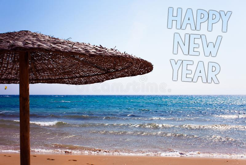 Writing note showing Happy New Year. Business photo showcasing congratulations Merry Xmas everyone beginning of January Blue beac. H sand message idea sunshade stock photo