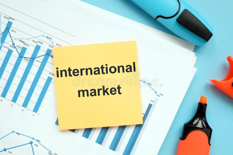 Writing note showing international market. The text is written on a small colored paper. Graphs on the paper sheet, markers, stock photo