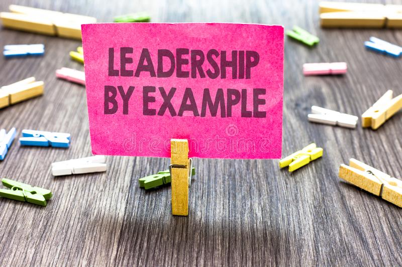 Writing note showing Leadership By Example. Business photo showcasing Becoming role model for people Have great qualities Multiple. Clips woody table small card royalty free stock photography