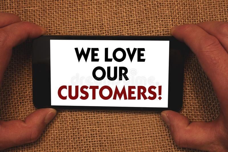 Writing note showing We Love Our Customers Call. Business photo showcasing Client deserves good service satisfaction respect Man. Holding cell phone white royalty free stock photography