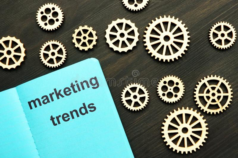 Writing note showing marketing trends. Small wooden gears, wooden background are on the photo stock photos