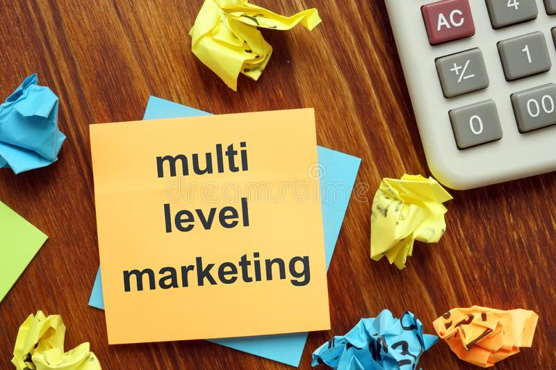 Writing note showing multi level marketing. The text is written on a small orange paper royalty free stock image