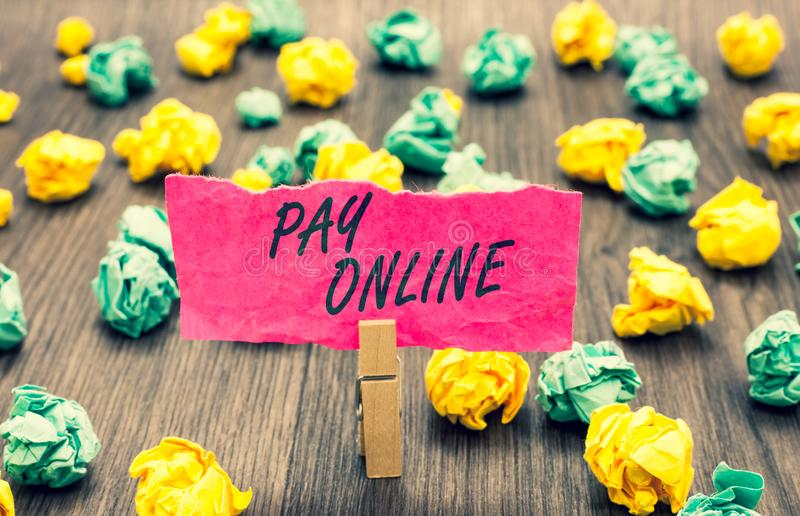 Writing note showing Pay Online. Business photo showcasing buy products or service using credit card on any website Clothespin hol. Ding pink note paper crumpled royalty free stock photography