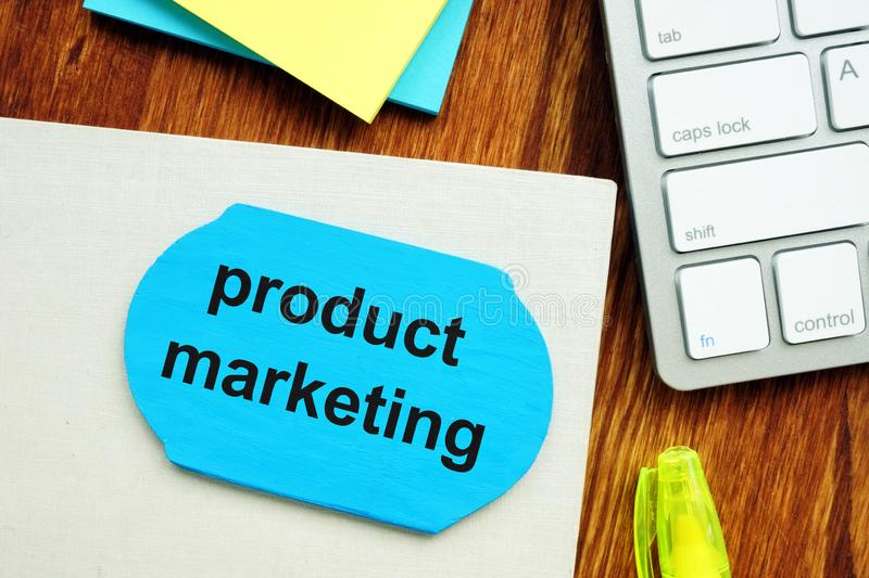 Writing note showing product marketing. The text is written on a small wooden board. Paper sheet, markers, keyboard, wooden royalty free stock images