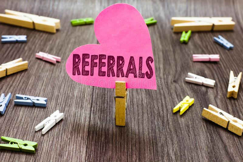 Writing note showing Referrals. Business photo showcasing Act of referring someone or something for consultation review. Clothespin holding pink paper heart royalty free stock image